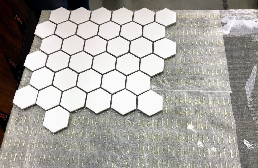 ceramic tile being laid on Simple Mat