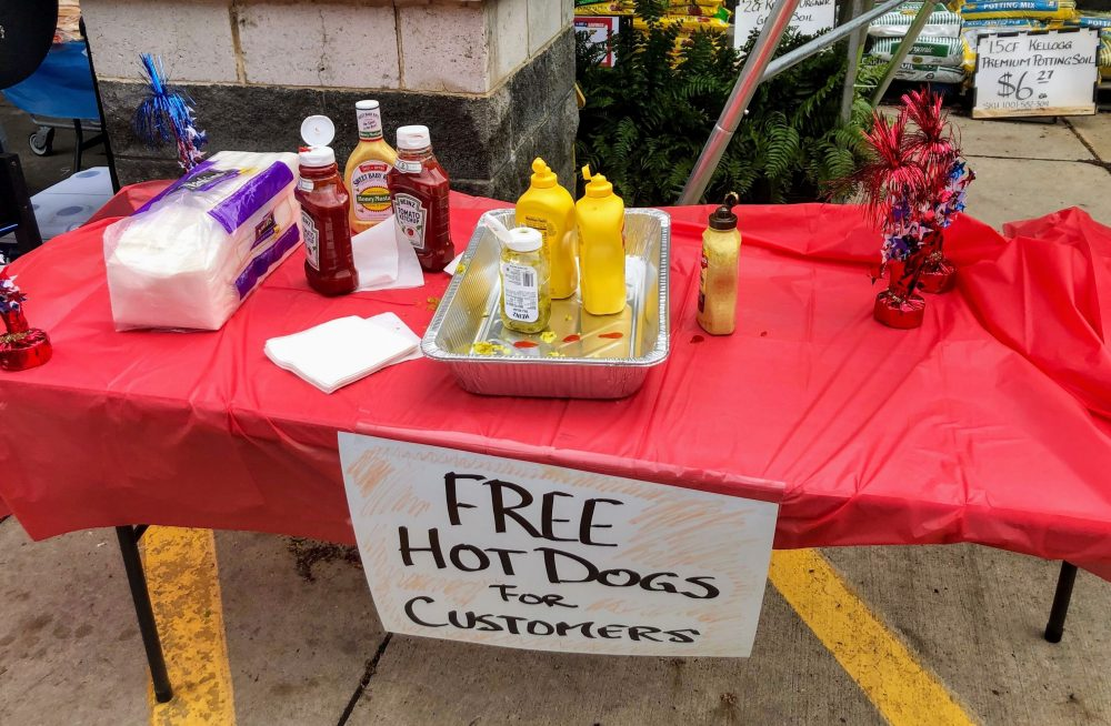 table outside of home depot with condiments for hot dogs