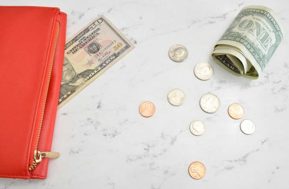 flat lay of orange clutch on table with money