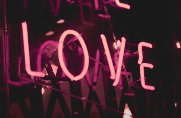 neon pink sign that says love