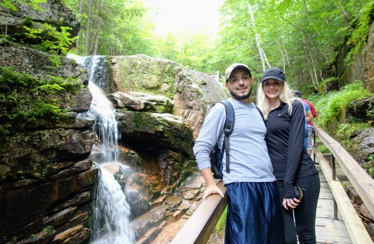 couple standing in front of a waterfall in New Hampshire