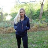 blonde woman standing outside in blue jacket
