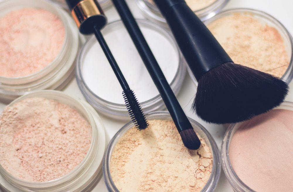makeup brushes laying on makeup powders